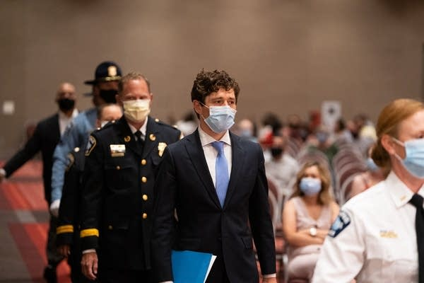 People wearing masks walk into a large room.
