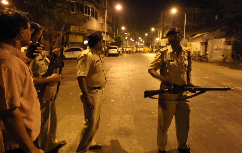 Indian policemen cordon off a shooting site