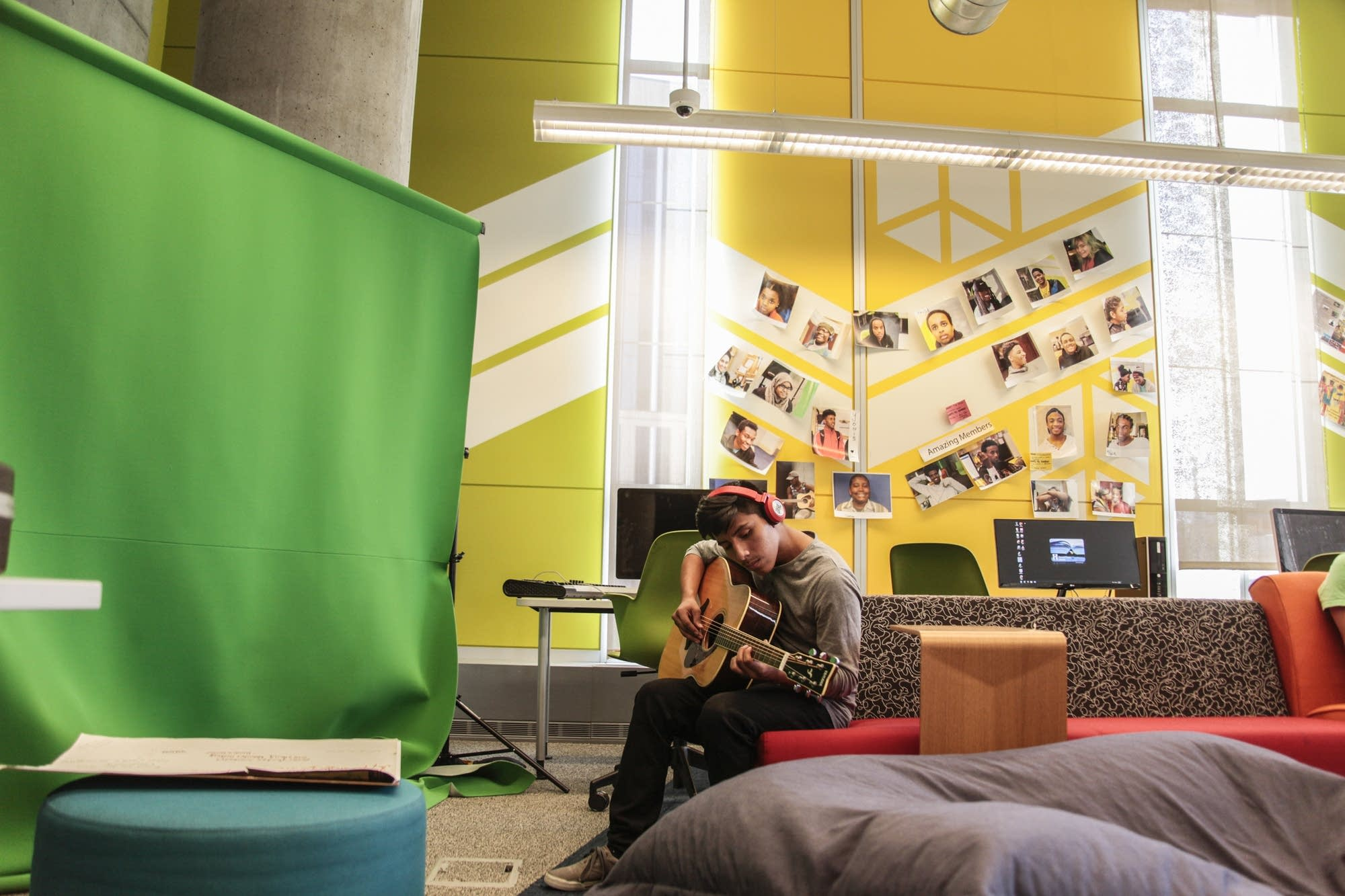 Donny Chiqui plays the guitar by the green screen at the teen tech center.