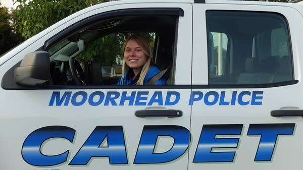 A woman sits in a police vehicle