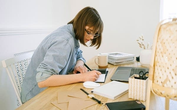A woman in a denim shirt working from home