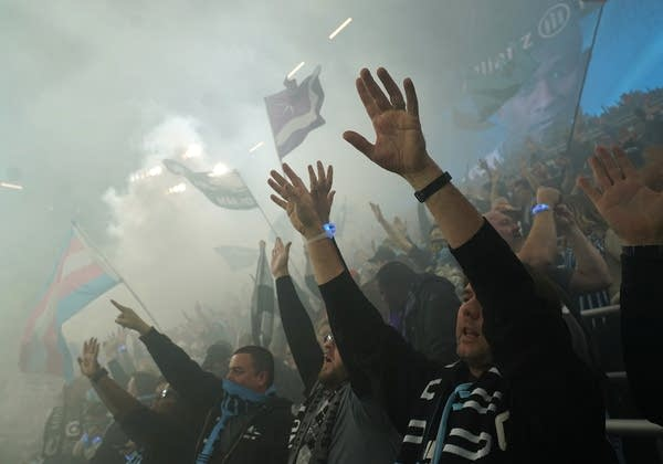 Fans raise their arms and wave flags through a fog of smoke.