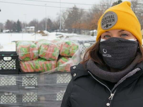 A woman stands outside with a face covering and a yellow winter hat.