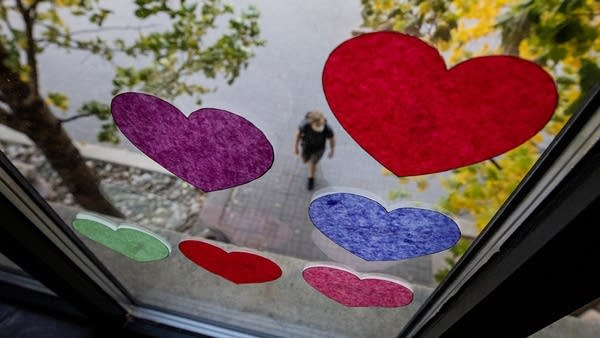 Paper hearts are taped the window of a building.