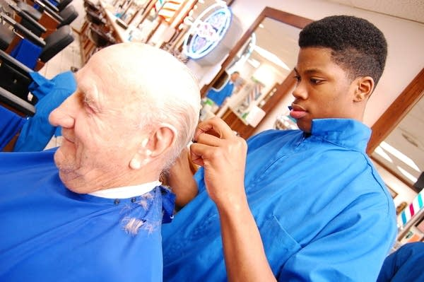 Barbering student with a customer
