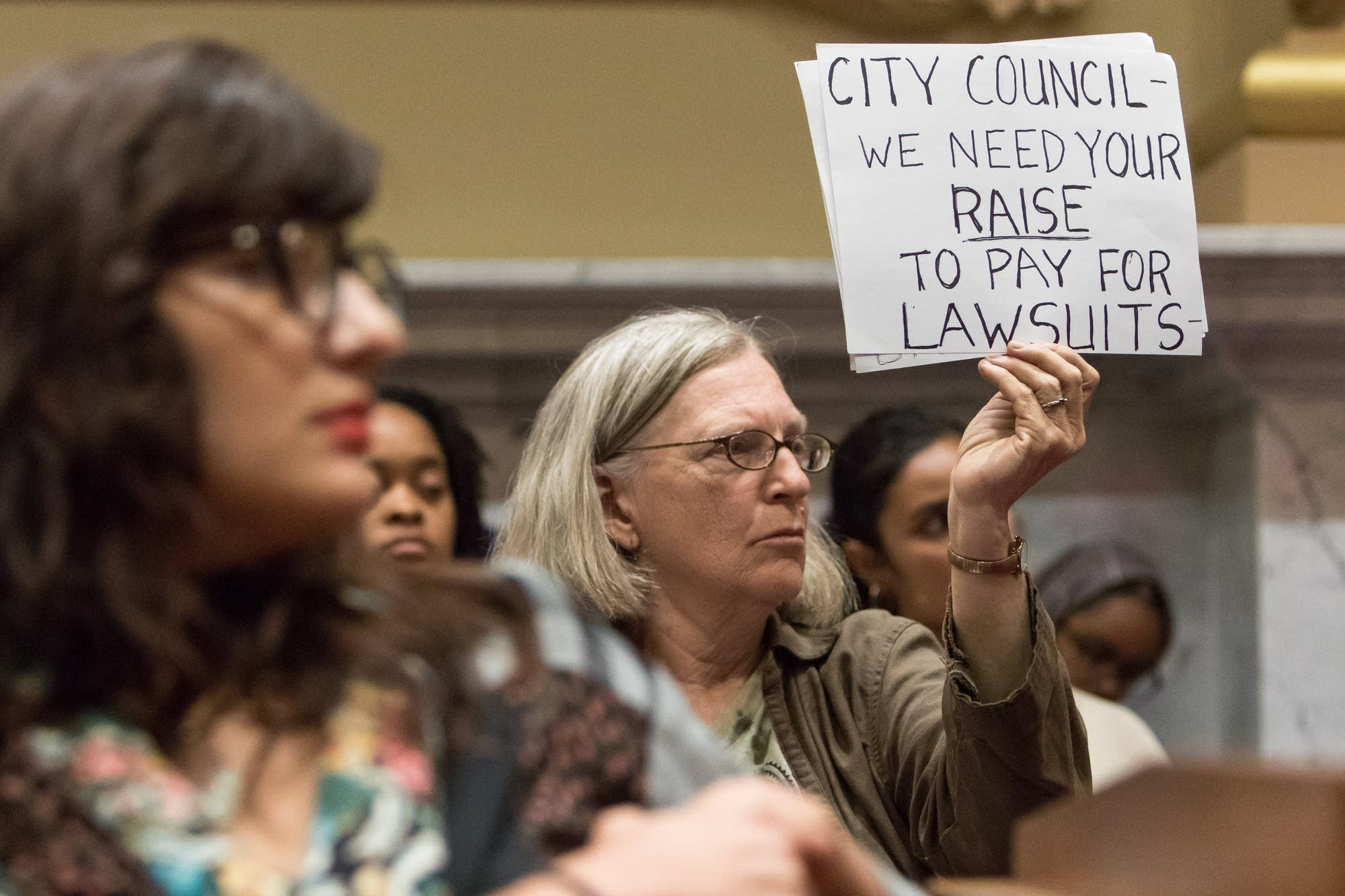 An attendee holds up a sign behind the speaker.