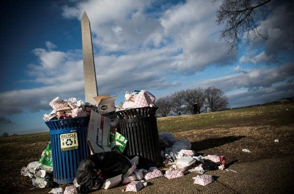 Litter spills out of a public dustbin next to the Washington Monument.