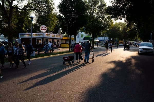Fairgoers walk down the street in the morning light.