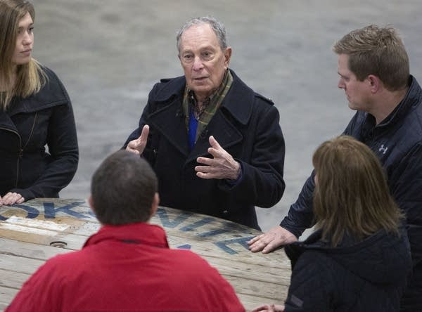 A group of people talk around a wooden spool table.