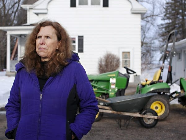 Noreen Thomas stands in front of her house in Kragnes Township, Minn.