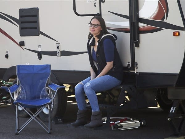 Lisa Neuburger poses by the camper she is living in