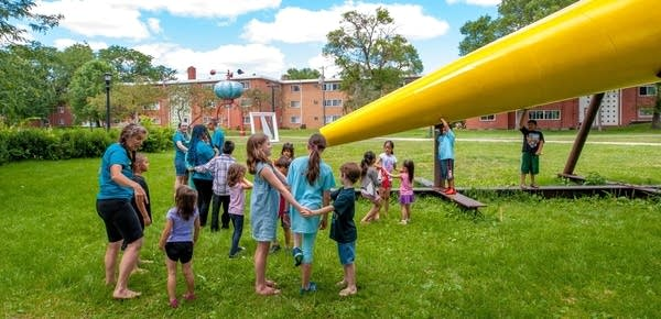 Children gather at a large yellow sculpture shaped like a megaphone