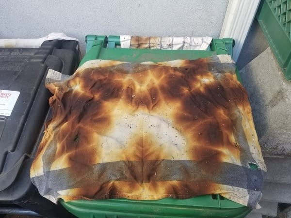 An old kitchen towel with brown burn marks all over it on a trash can
