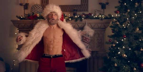 A young Santa, shirtless and fit, draped in a coat in front of a fireplace