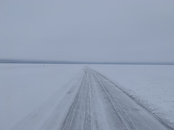 A road on a frozen lake fades into the distance