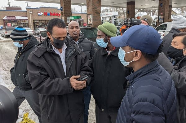 A group of people stand in front of a gas station.