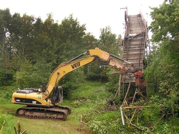 A demolition excavator pulls apart the jump.