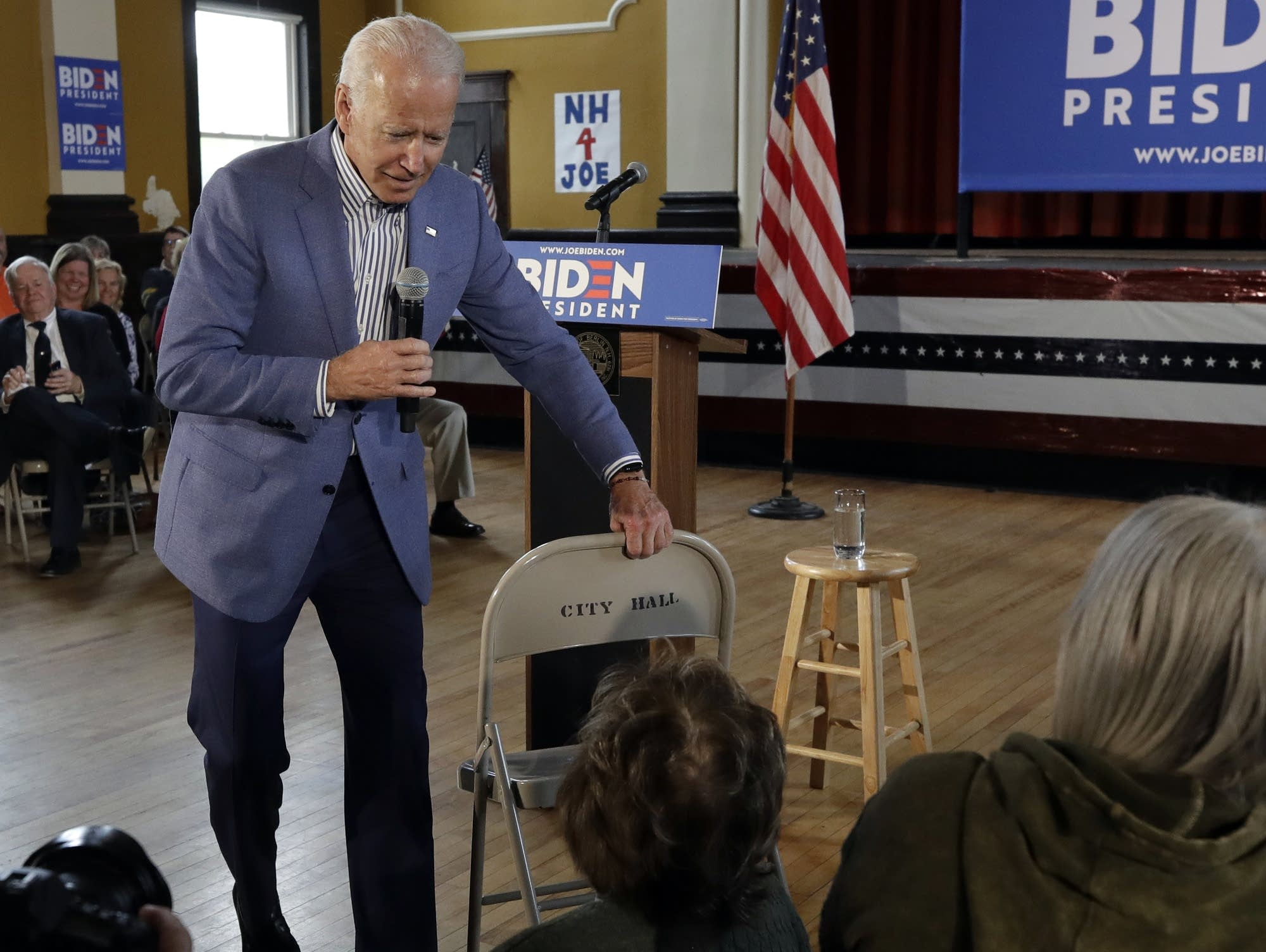Joe Biden brings a chair over during a campaign event