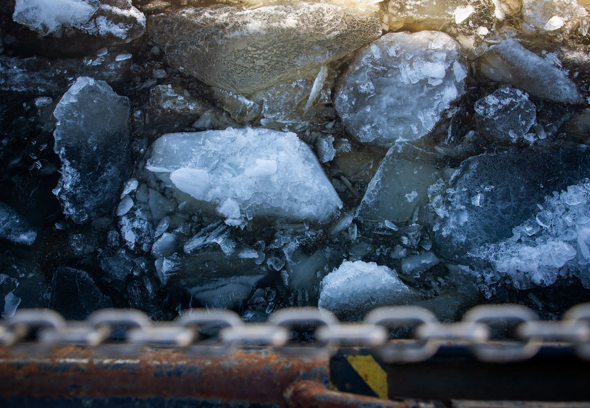 Chunks of ice as thick as a foot or more float by the ice cutter.
