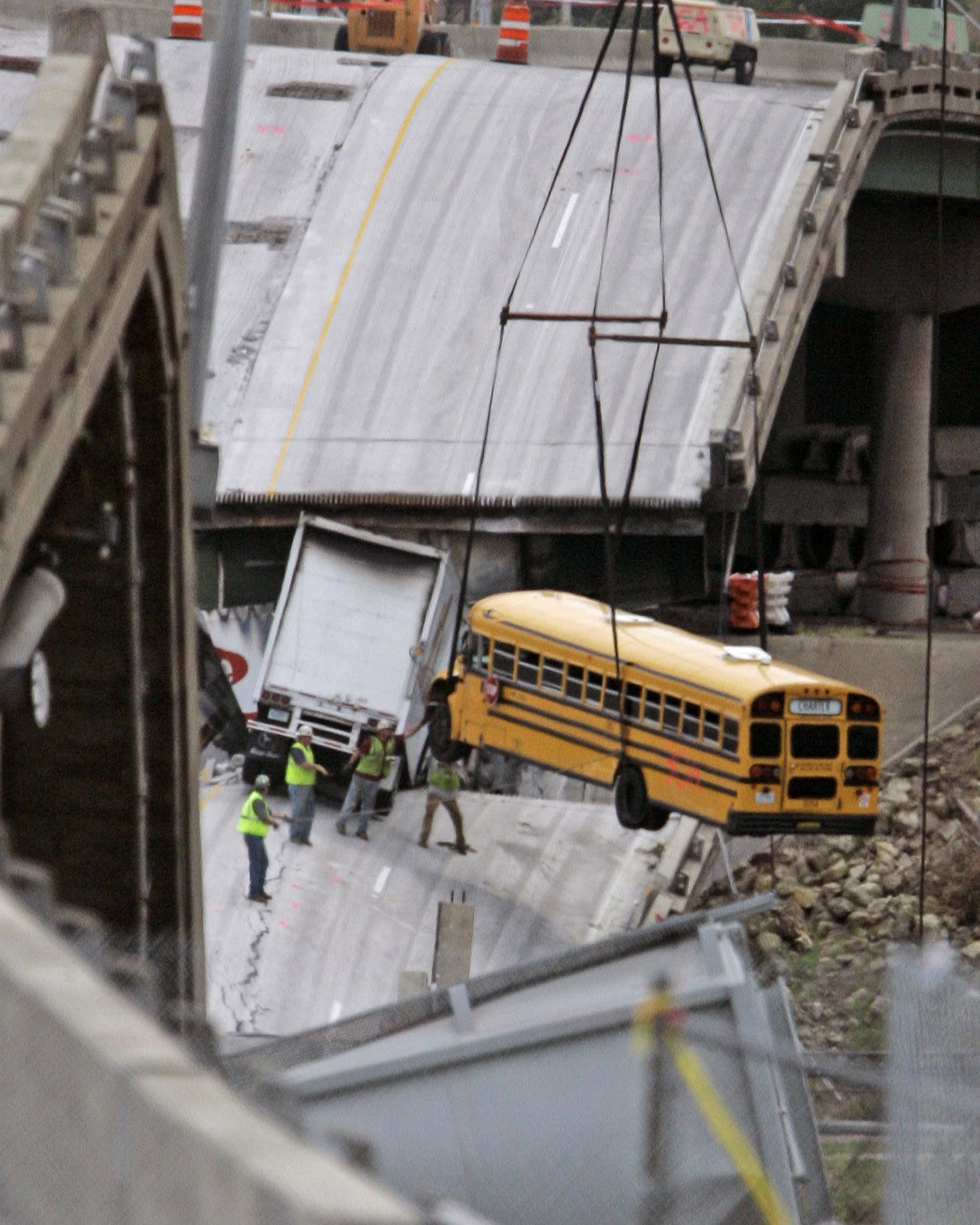 Workers remove a bus from the 35W bridge collapse