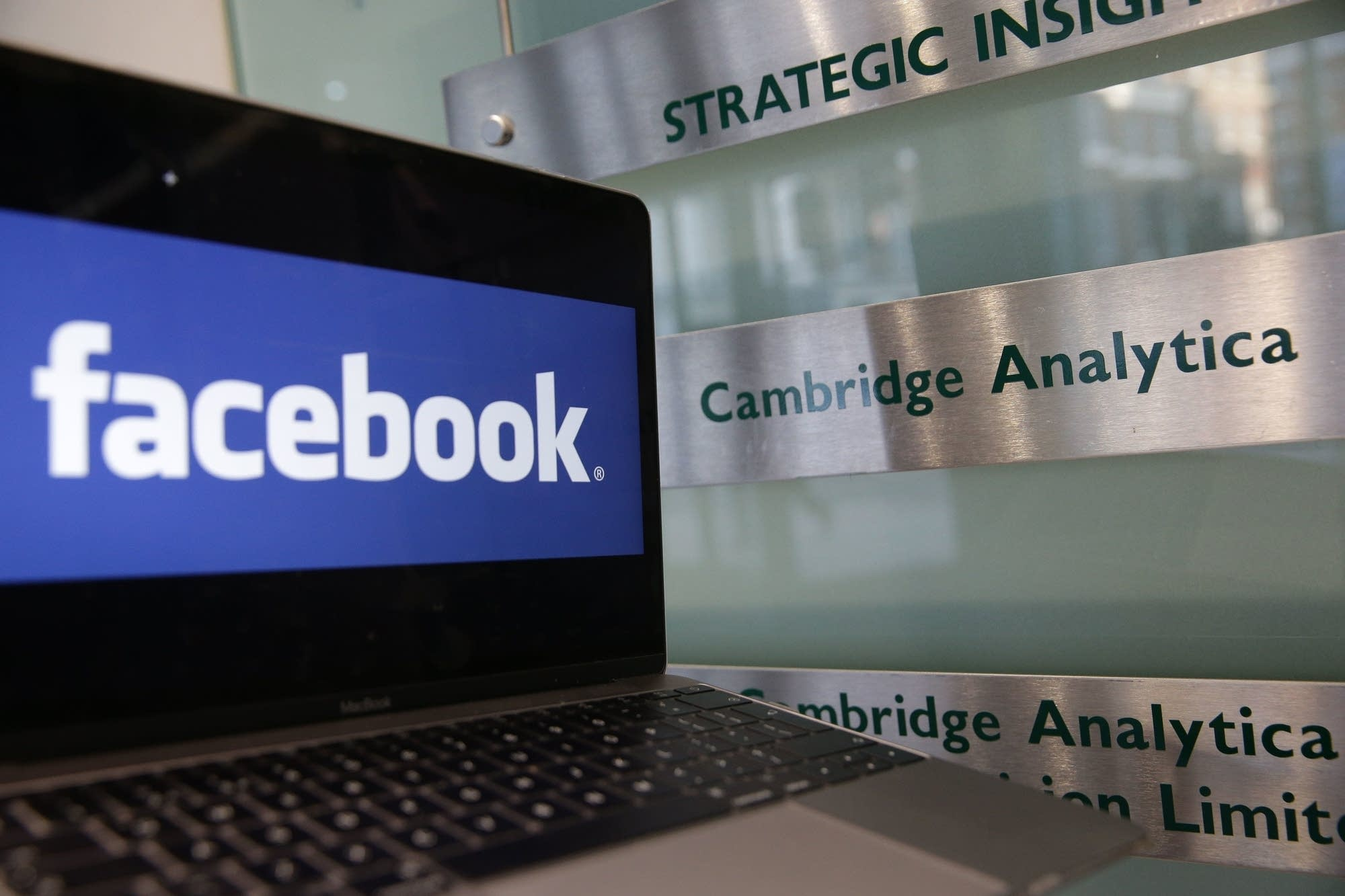 A laptop showing the Facebook logo alongside a Cambridge Analytica sign.