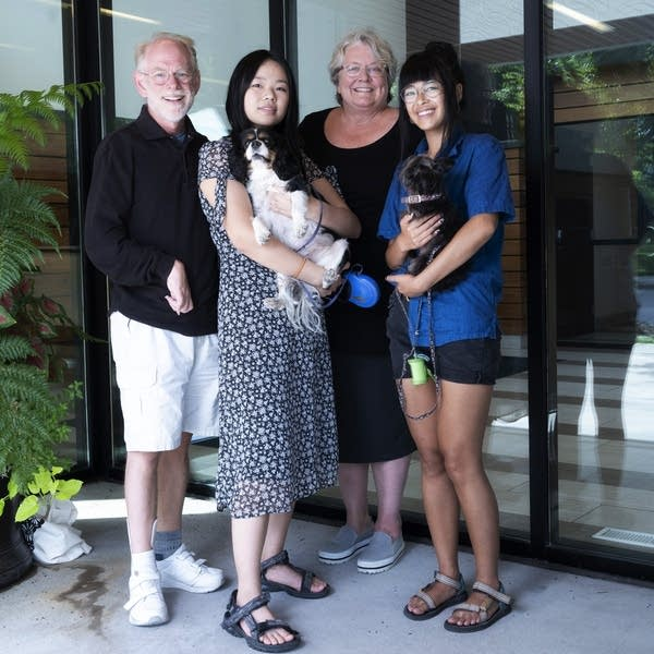 A family of four poses for a photo. Two girls are holding small dogs.