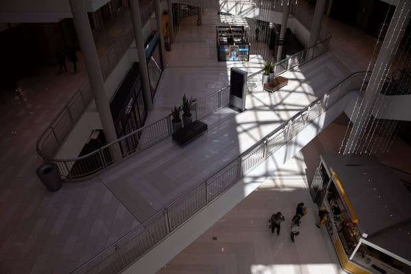Light shines on a nearly empty mall.