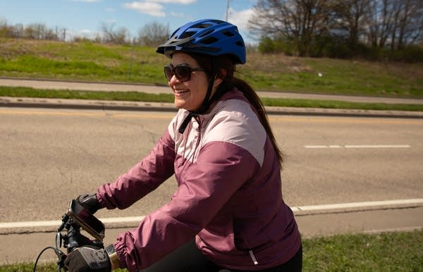 a woman rides on a bike path separated from vehicle traffic