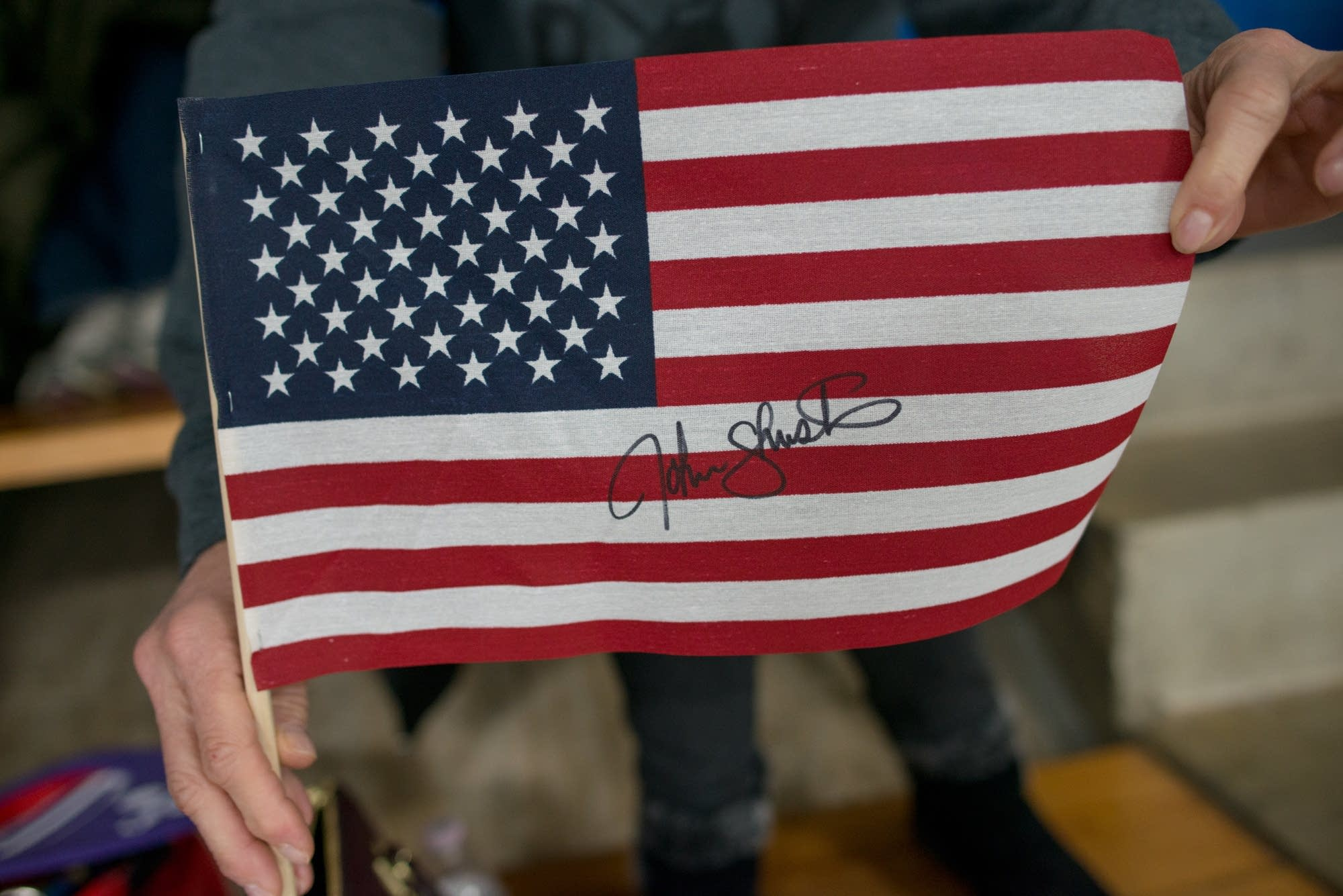 Ginny McDonald displays a flag signed by John Shuster.