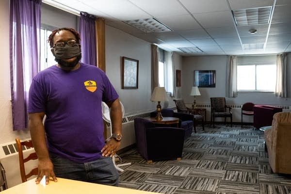 A man in a purple shirt stands in a room.