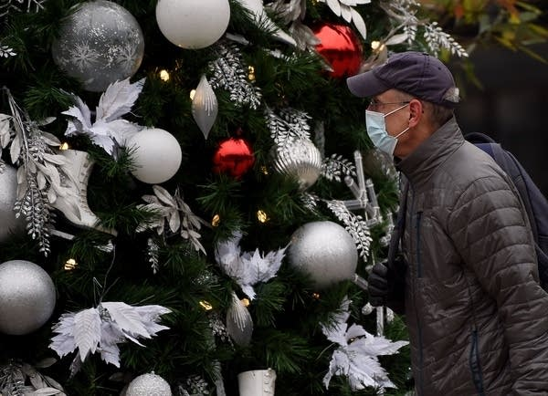 A man wearing a face mask walks past a decorated Christmas tree.