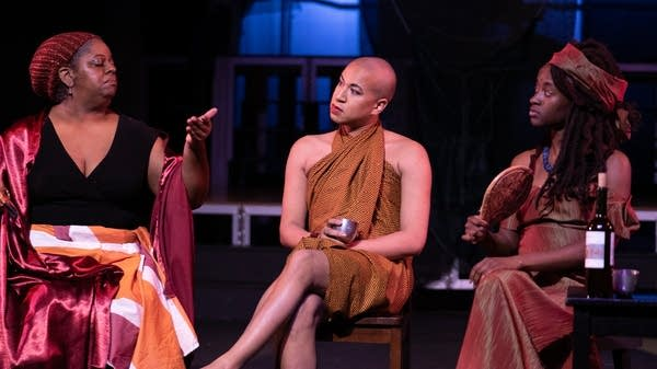 Three people sit on a stage in conversation.