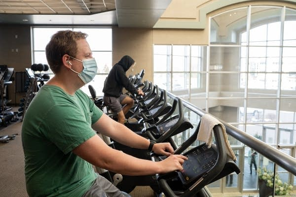 A man in a mask rides a stationary bike.