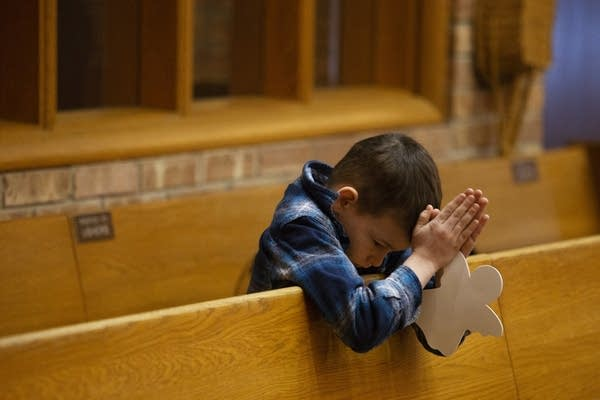 Kyle Jr. Peltier prays during Sunday service.