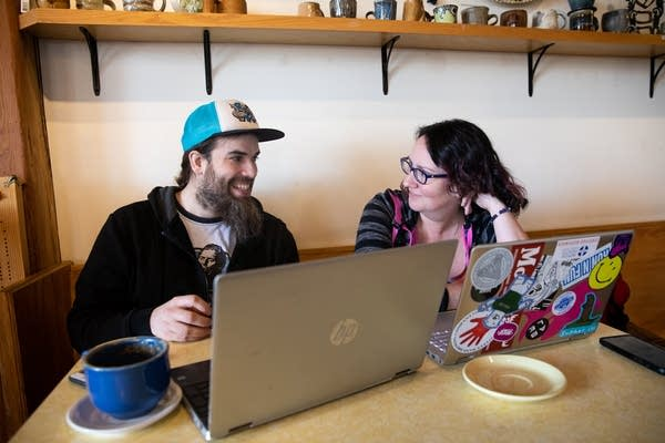 Two people sit at a table with laptops.