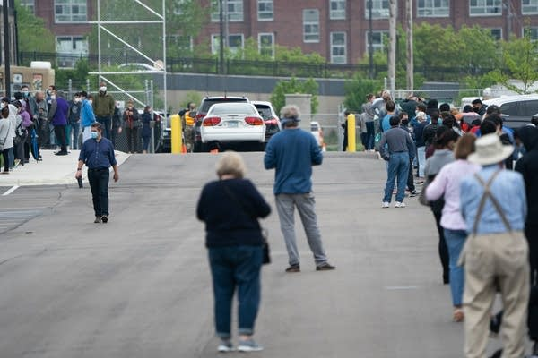 People stand in line in a parking lot.