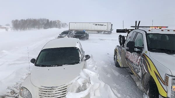 A jackknifed semi, stranded cars and snowdrifts block State Highway 60