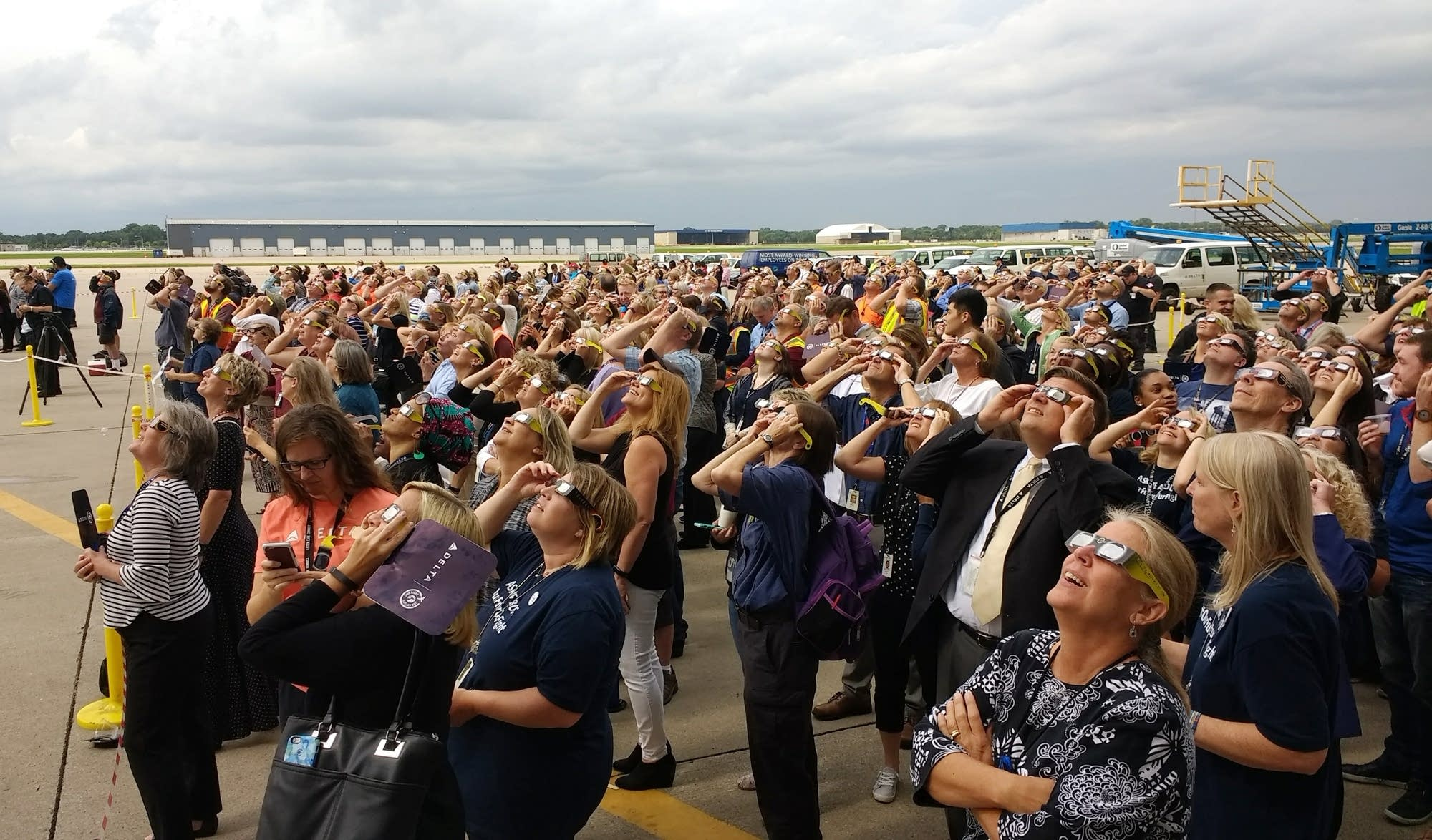 Airport employees stand outside to watch the eclipse.