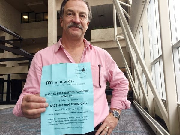 Bob Shoenberger, founder of Minnesotans for Line 3, display a PUC ticket.