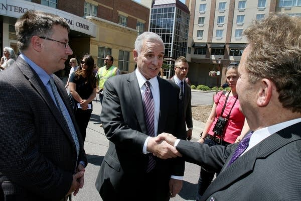 Gov. Mark Dayton shakes hands with local officials