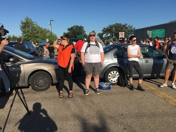 Protesters block cars near the Bishop Henry Whipple Federal Building.