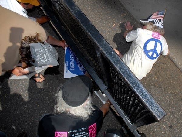 A protester crawls under a security fence