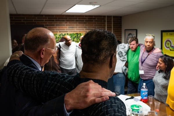 Paul Schnell stands in a circle with formerly incarcerated men/