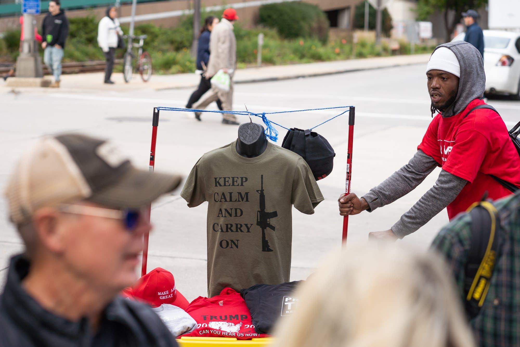 A vendor pushes a cart of Trump merchandise.
