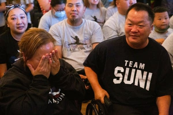 A close-up photo of family members as they react to Sunisa's performance