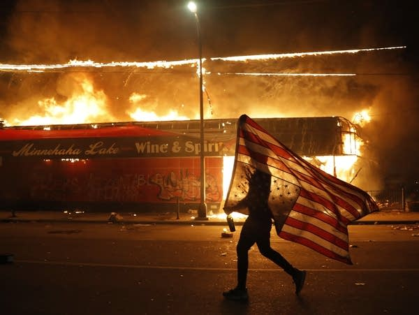 A protester carries a U.S. flag upside down next to a burning building