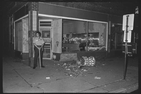 Black and white, a police officer stands near a store front.