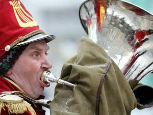 A musician warms up his tuba on a cold day.
