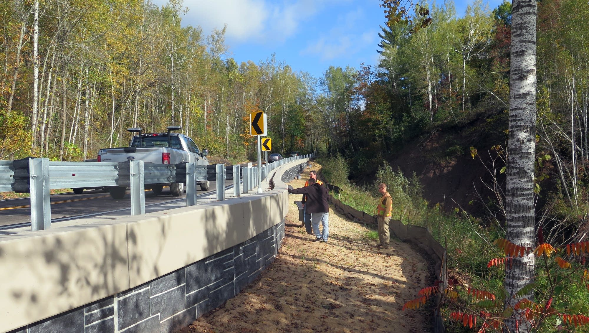 Officials inspect a retaining wall along a repaired section of Hwy. 210.