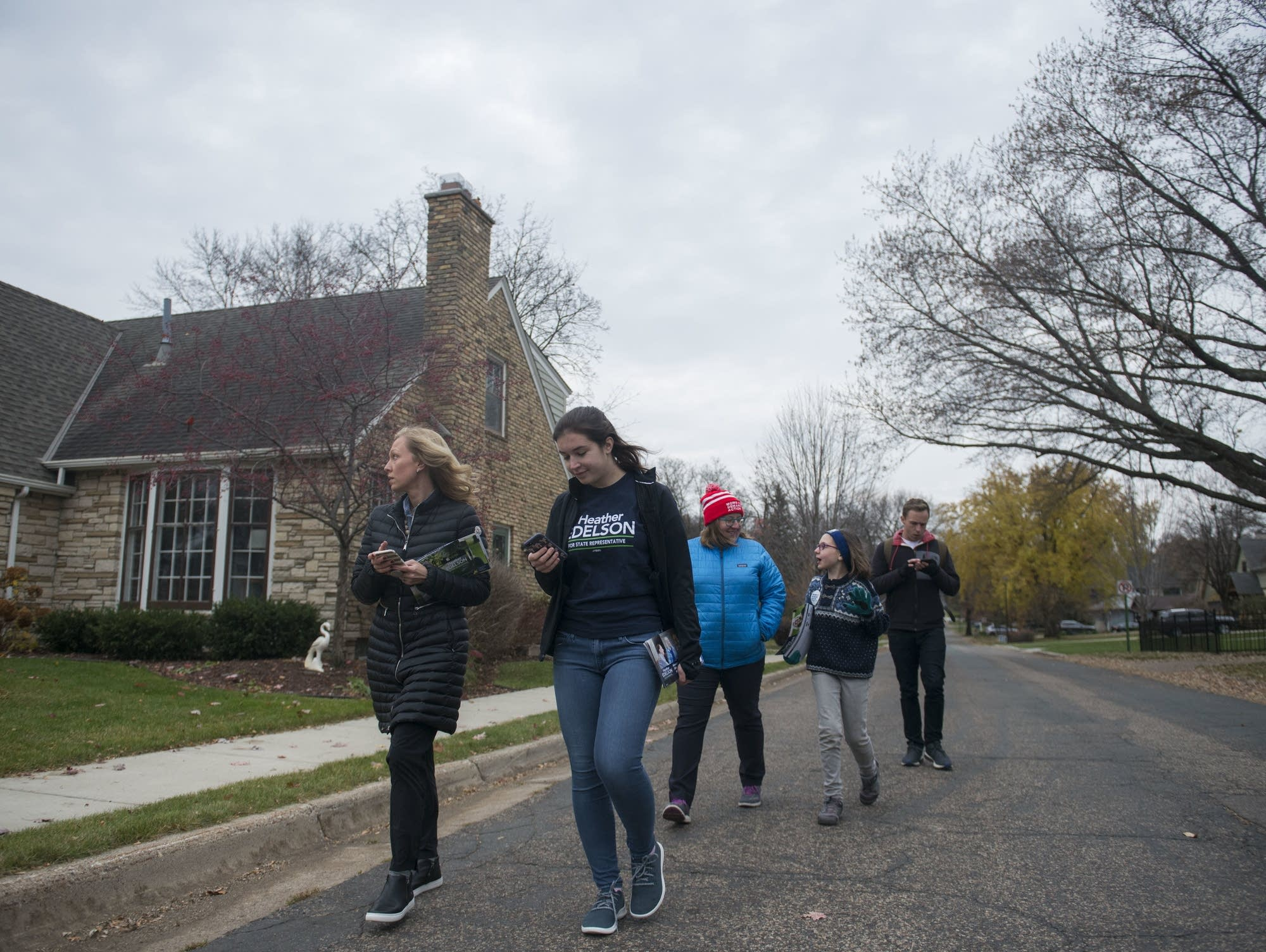 Heather Edelson walks down the street with her staff in Edina
